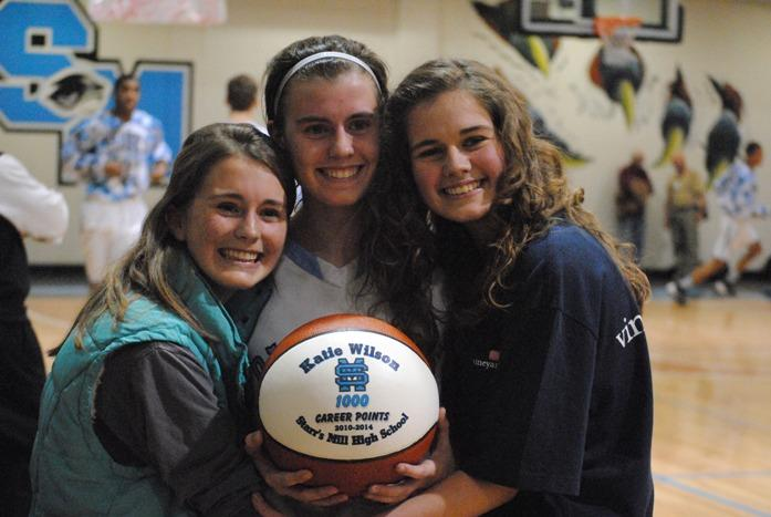 Senior Katie Wilson (center) takes a picture with her 1,000 point commemorative basketball. With her are her two sisters, Meghan (left) and Natalie after the game against Whitewater.