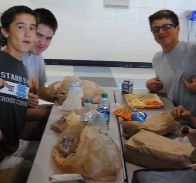 Sophomores Connor Donahue ( far left)  and Jake Odom (left), eat their filling sack-lunches during B lunch. Nick Palmer (right) eats a school lunch consisting of garlic French bread pizza, some  carrots, and a bag of Cheetos.