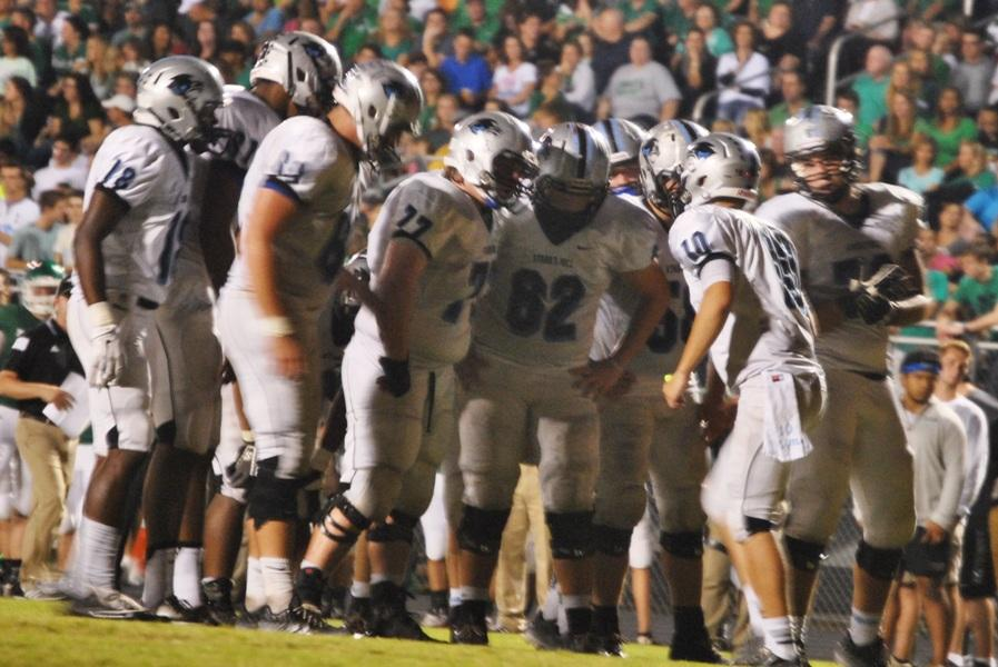 Sophomore quarterback Stone Kasten speaks to his offense in the huddle during the second quarter of the Panthers' win over Mcintosh.