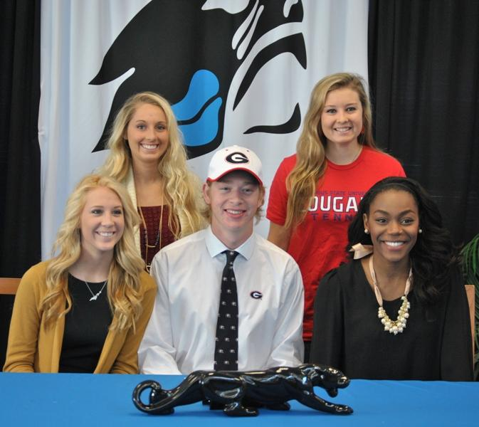 Natalie Orcutt (from left), Megan Binkley, Adam Goodman, Rachel Williams, and Danielle Ajayi gather in the Media Center to sign their letters of intent with their colleges.