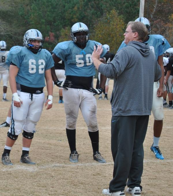 Offensive-line coach Frank Maguire shows how to block effectively in preparation for Friday nights playoff game against Ware County