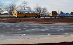Buses roll out of the South Complex after the last bell, passing the completed golf cart parking lot.