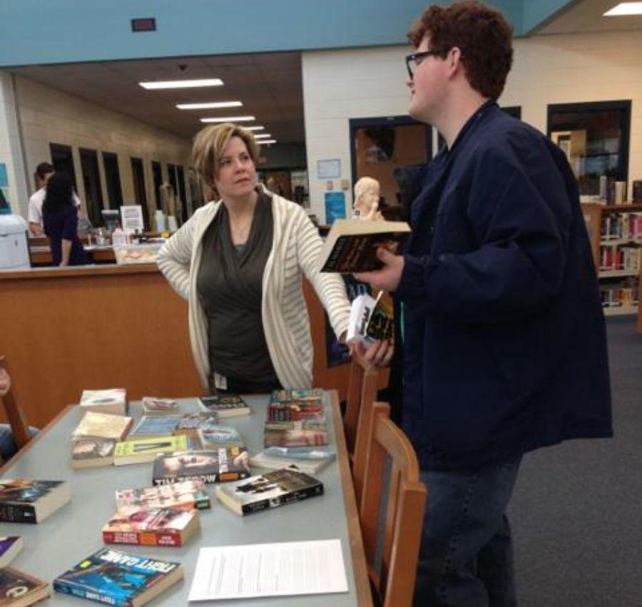LeighAnne Hanie discusses the books at the book swap during