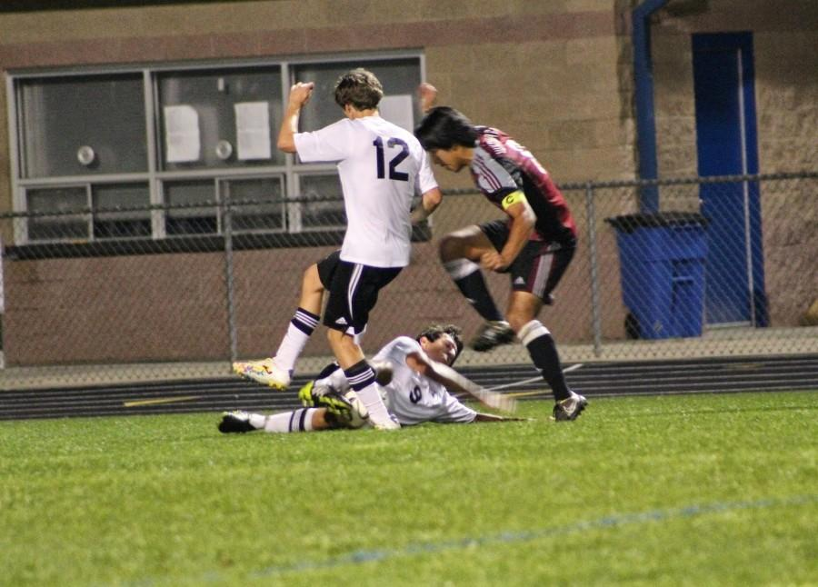 Seniors Tyler Annis (12) and Armon Varmeziar (9) draw a tackle to challenge the Whitewater midfielder before he could shoot on goal.