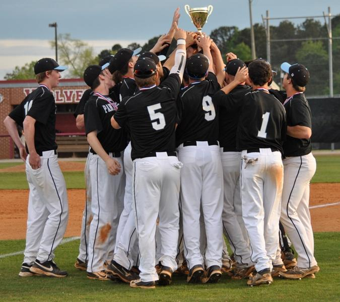 The Panthers huddle around the Region 4-AAAAA Championship trophy after their 5-4 win over Union Grove last Thursday. It is the sixth time the school has won the trophy.