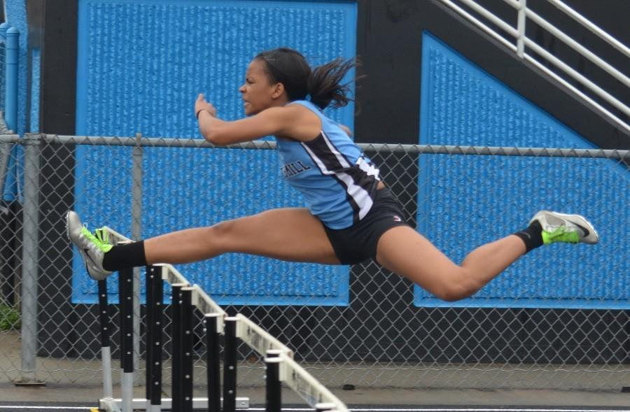 Junior Alexis Farley competes in the hurdles events during the county championship on March 14.