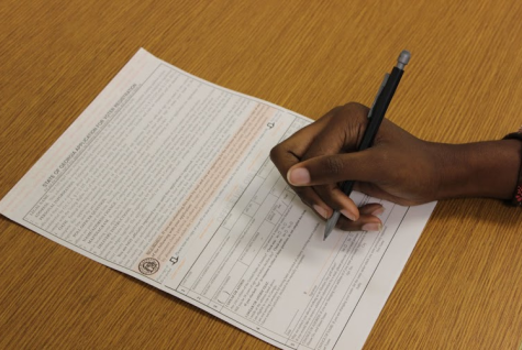 A student fills out the Georgia Voter Registration form. These forms are available in the Guidance Office.