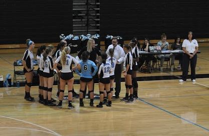 Volleyball coach Walt Ellison huddles with his team to discuss strategies during a time-out in their game against Northgate on Sept. 1.