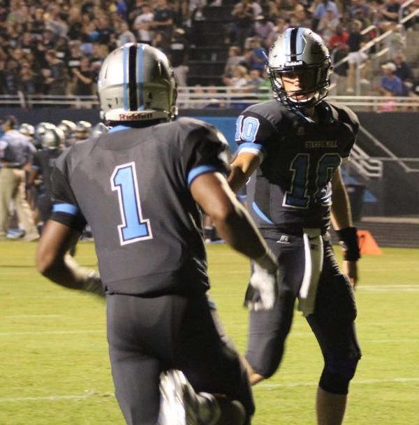 Sophomore quarterback Joey DeLuca congratulates fellow sophomore running back Rico Frye after a touchdown run in the third quarter.