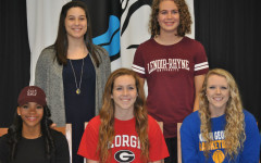 Five Panther athletes smile after they sign their college letters of intent. The signing took place at 9 a.m. on Nov. 12 with parents, coaches and administration in attendance.