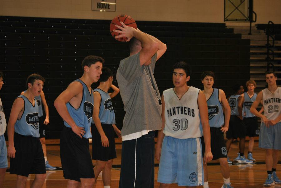 Head coach Brandon Hutchins explains shooting techniques and basketball strategies to his players.