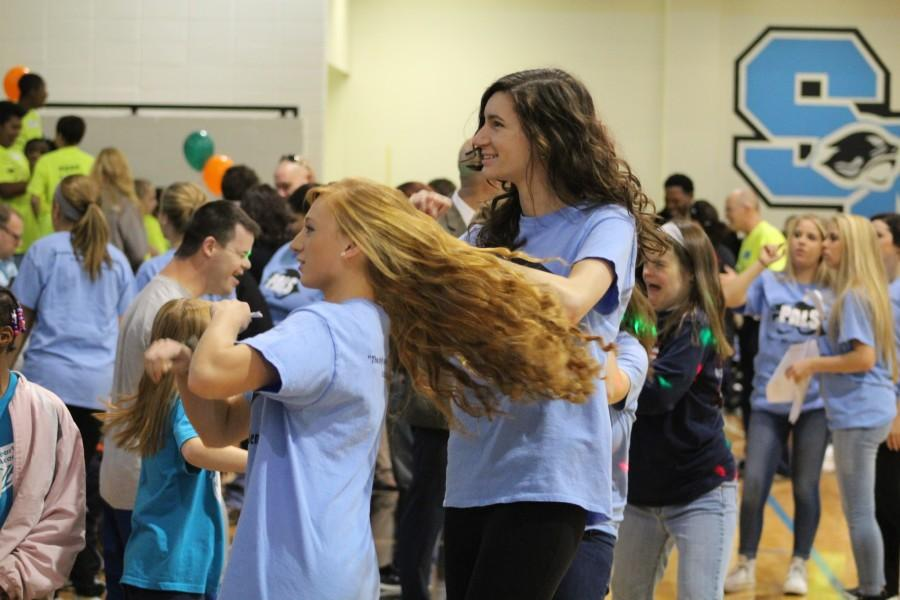 Students volunteers at Special Olympics dance in the gym before the basketball games begin.