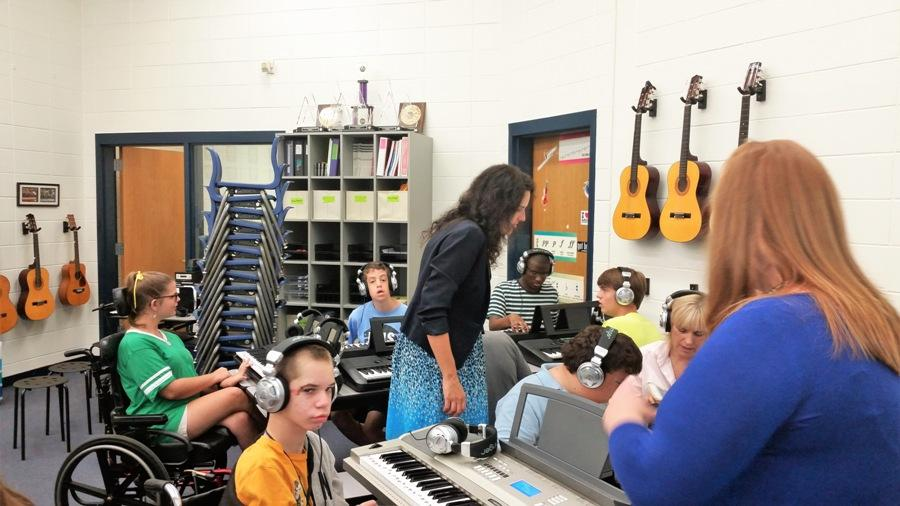 "Middle school chorus teacher Christy Todd and adaptive curriculum specialist Courtney Savage assist the students in playing piano. ""Music is a huge part in the way I teach the curriculum,"" Savage said."