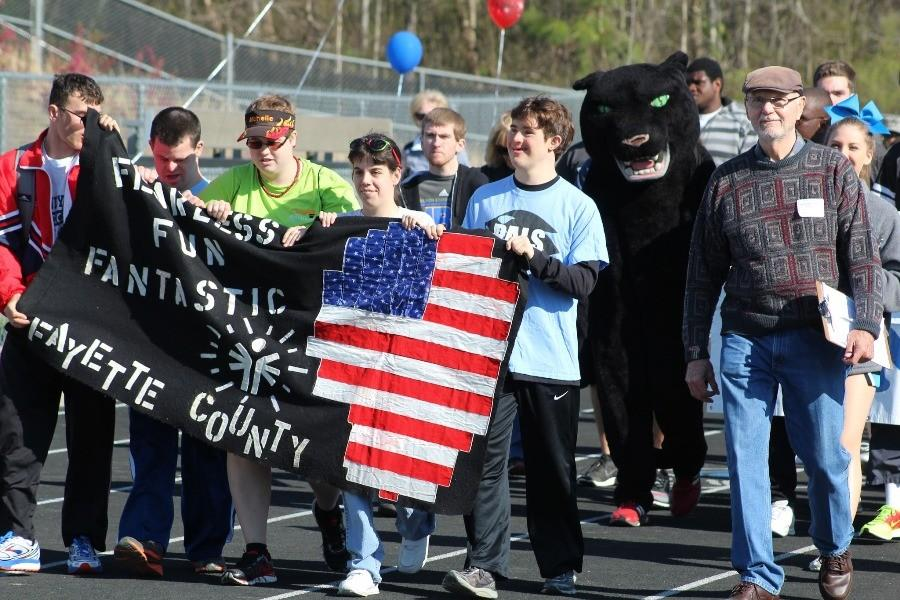 Special olympic alumni athletes lead the Special Olympics parade for the beginning of the opening ceremonies on March 23. During the parade, all schools were introduced while athletes, teachers and student volunteers walked once around the Panther Stadium track.