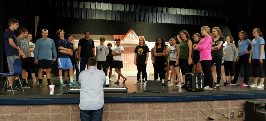 """Before rehearsing a dance, the full cast runs through the vocals of the number with and without music to prepare. Musical director Zachary Stutts reminds the students, """"If you have fun, it'll sound fun, and you'll enjoy it that much more."""""""