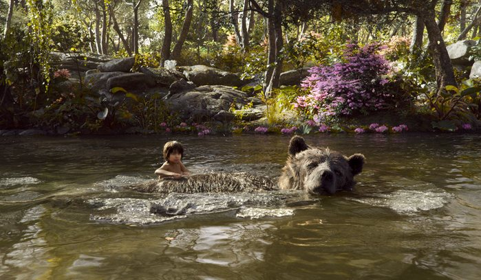 """Mowgli (Neel Sethi) and Baloo (Bill Murray) float down the river singing the """"Bare Necessities."""" Regardless of slight changes to the story, the song ties together some of the similarities between the cartoon and the new live-action film."""