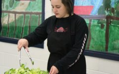 "Culinary arts student works the salad bar the week before spring break at ""Salads and Spuds,"" a faculty luncheon set up by nutrition and wellness teacher Cheryl Clower. Students gave a survey to 40 teachers to create the menu, and teachers spent $7 for their meal."