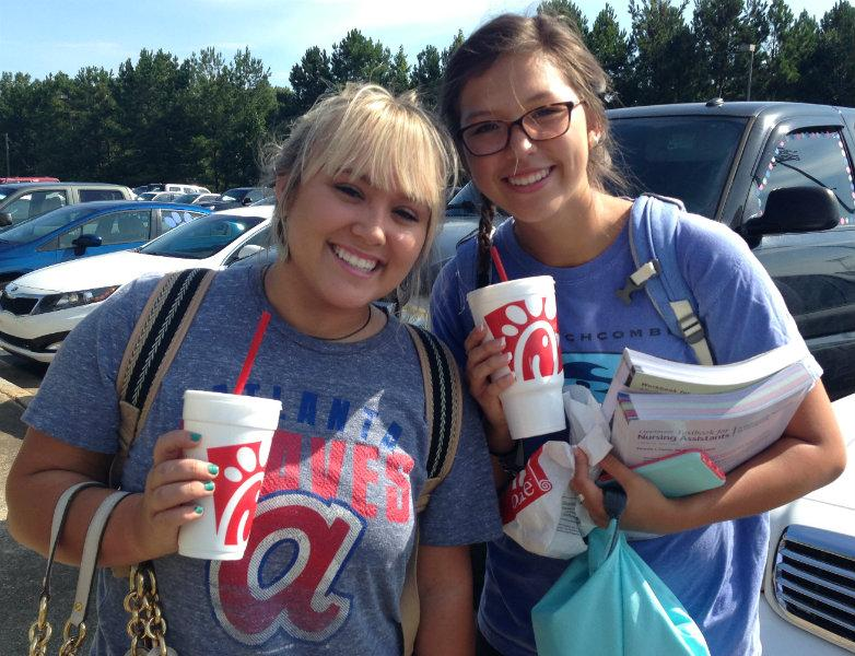 """Ready to start their morning right, two students walking to check-in have smiling faces with Chick-fil-A in hand. """"I think I enjoy Chick-fil-A so much because it offers quality fast food,"""" senior Michaela Cushing said."""