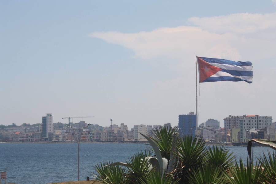During mid-day, the Cuban flag waves in the wind by the harbor overlooking Havana, Cuba.