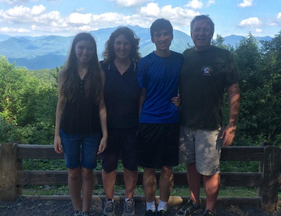 The Kelly family pose for a family photo while visiting Gatlinburg, Tennessee, for the first time.  The parents do their best to share the housework equally and support gender equality in the household.