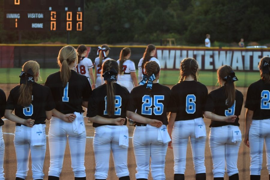 The Lady Panther varsity softball team lines up on the first base foul line for the National Anthem. The Panthers were defeated by the Whitewater Wildcats 8-3 on Tuesday night.