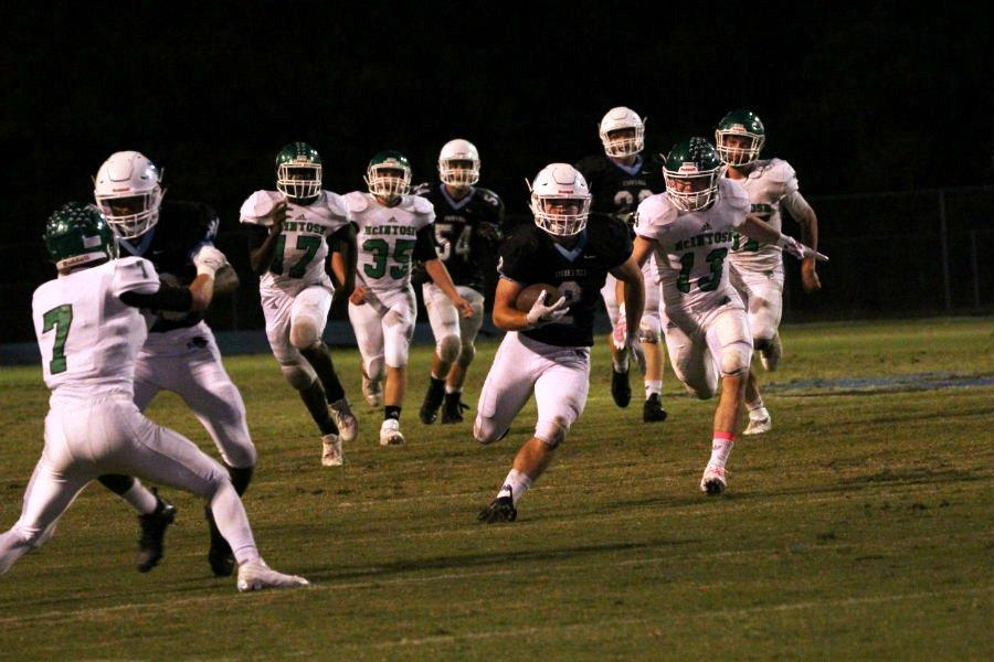 Junior running back Cole Gilley races past the McIntosh defense during Friday night's 28-7 victory. Gilley ran for 137 yards against the Chiefs, becoming the first running back in the region to pass 1,000 rushing yards this season.