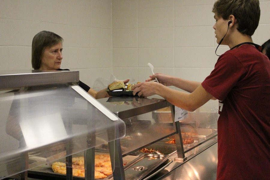 """Margaret McClain serves a student lunch. """"We love seeing the students. That's the favorite part of our day, when we get to see them and when we make them happy by serving them what they want,"""" lunchroom manager Maureen Hankey said."""