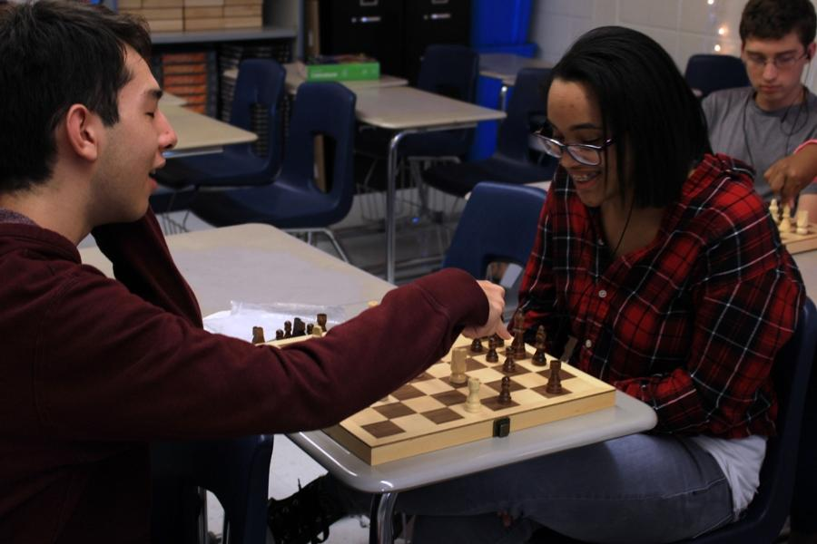 Two members of Chess Club name the different pieces on the board. The club is open to all students and meets twice a month in English teacher Katherine Tucker's room 720.