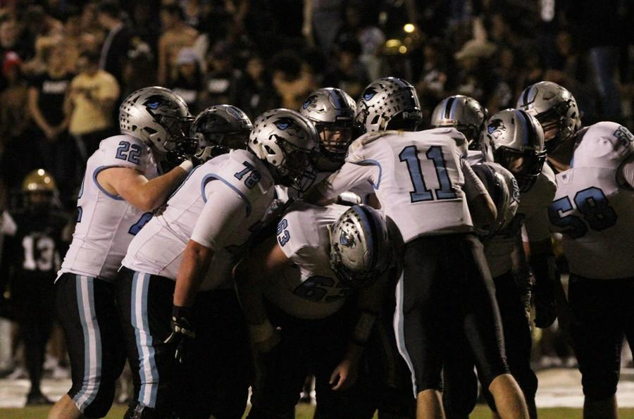 """Panther offense huddles before a play against Fayette County. """"I think this game was probably the best game [the offensive line] has had all year,"""" junior quarterback Joey DeLuca said."""