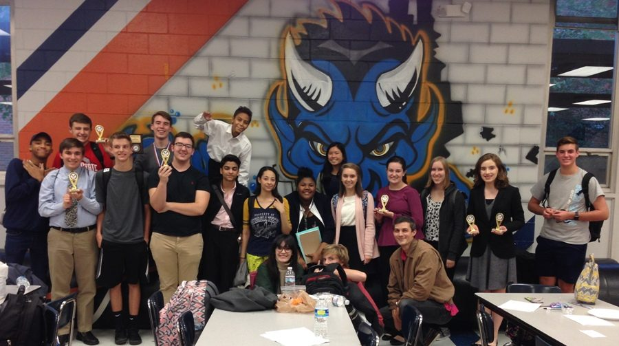 """Debate coach and English teacher Brandon Kendall (lower right) poses alongside debate team competitors after the tournament at Columbus High School on Oct. 22. """"There are a total of 45 members of debate team, but we usually take 30 to 35 students [to each tournament],"""" Kendall said."""