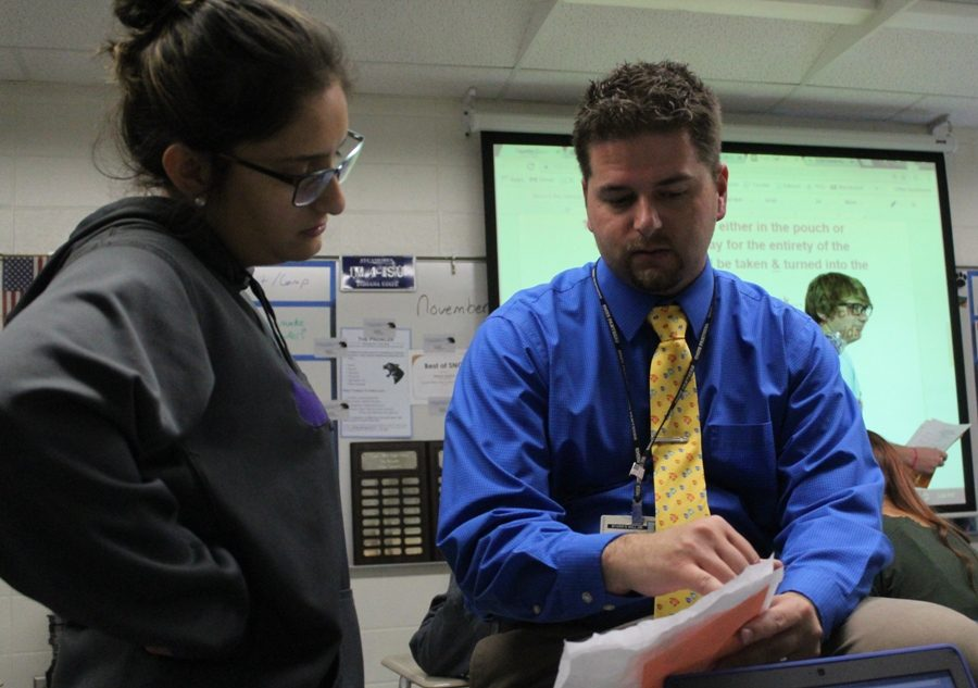 """English teacher, creative writing teacher, and journalism adviser Justin Spencer helps explain a concept in his 10th grade Literature and Composition class. """"Man, teaching is great. Working with students, interacting with students, sharing conversations, sharing ideas, laughing, and making it enjoyable [is what I love about teaching],"""" Spencer said."""