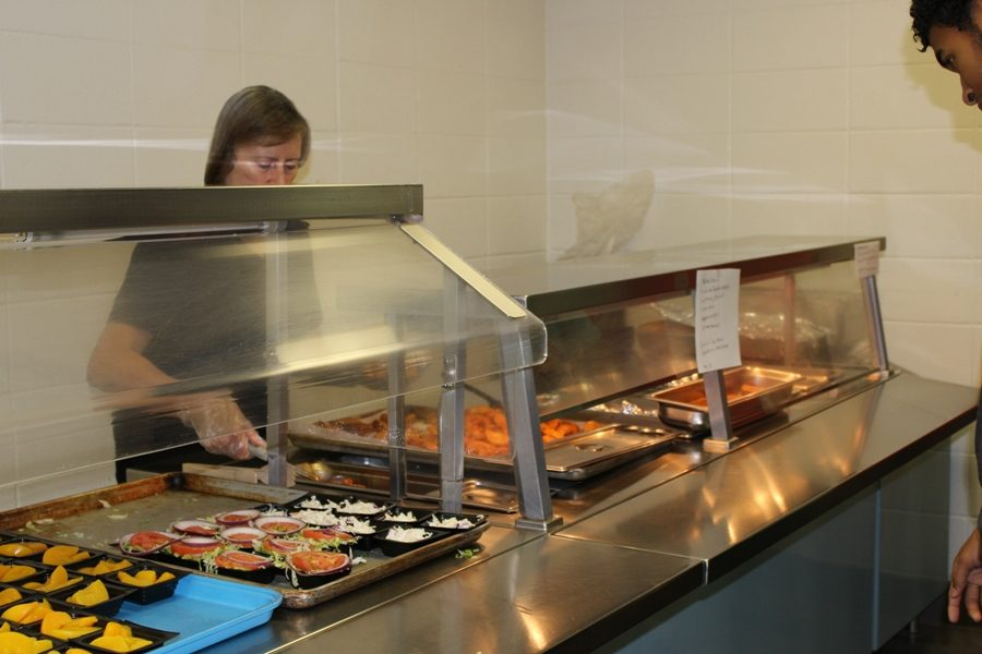 Member of the cafeteria staff serves a Starr's Mill student lunch. The process to approve the lunch options on the menu take place at the federal, county, and school levels.