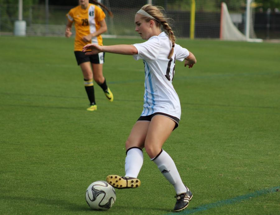 Senior Ashley Broderick kicks the ball while running from a defender. Broderick also won the Heisman Award, and continued on into the final round for state.