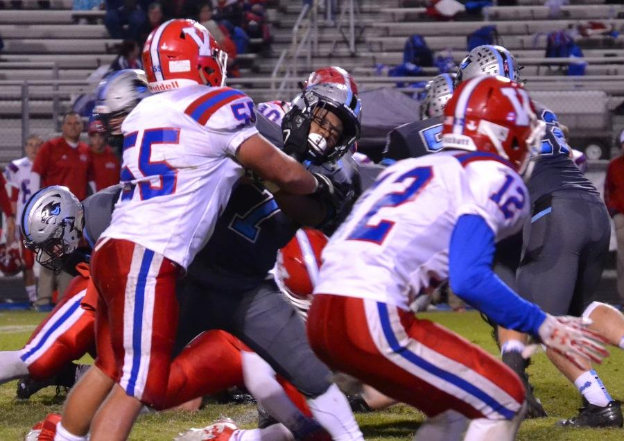 Brown blocks a Warhawk defender during a run in Friday's game. All of the running backs worked together to gain 330 yards on the ground against Veterans.