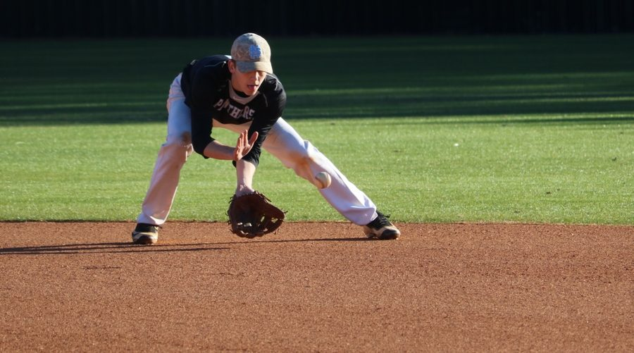 Junior Mitchell Sutton fields a ball at shortstop. The varsity boys play their first home game March 2 against Morrow.
