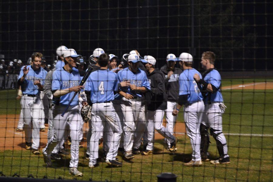 The Panther varsity baseball team gathers at home plate after senior Will Evans hit a two-run home run in the bottom of the first. The Panthers defeated the Wildcats in a 15-run mercy rule in the bottom of the third, improving their overall record to 8-1.
