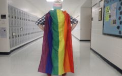 Gay Straight Alliance club member stands in the hallway wearing a transgender flag beanie and the gay pride flag as a cape. The GSA club strives to encourage sexuality and gender diversity in the school.