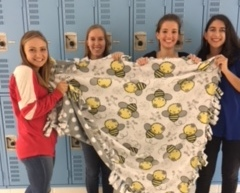 Junior Ally Marshall and seniors Erin Rathje, Marleena Tamminen, and Elena Wernecke hold up the blanket they created for the service project. The blanket, along with a photo of Spanish Honor Society members, will be donated to the children's hospital.