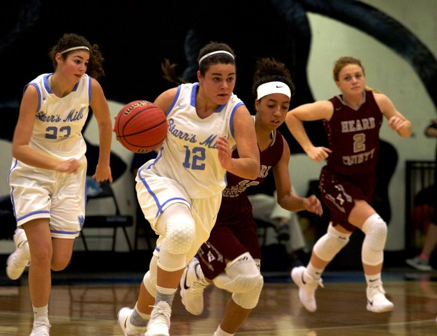 A junior player dribbles the ball up the court during a fast break. The Lady Panthers were able to score in transition due to spectacular rebounding.