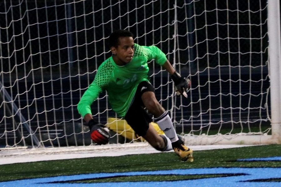 """Freshman keeper Andrew Cole saves the ball as it is shot his way. """"I try to organize [the team] as much as I can and tell them where to be,"""" Cole said. """"I always have the best view of the field."""""""