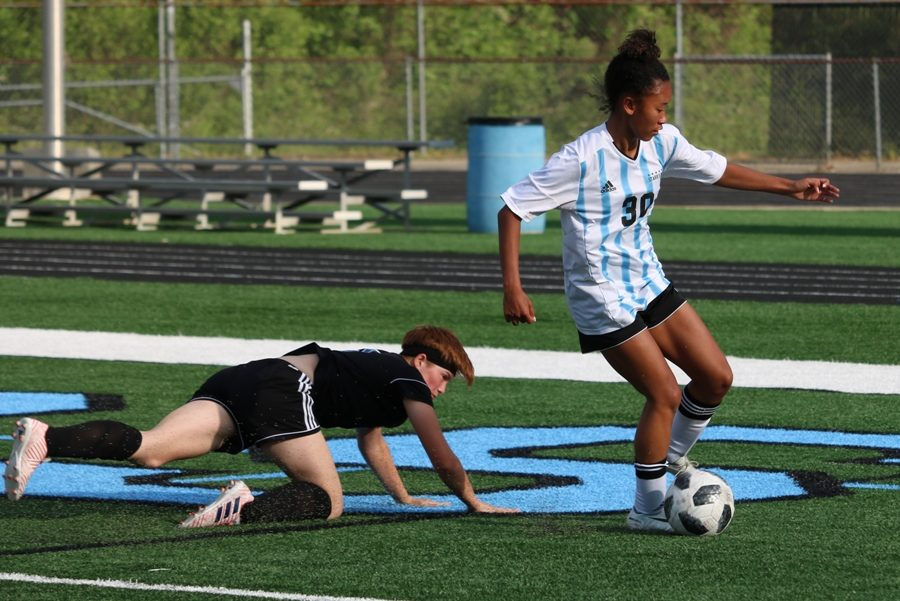 Lady Panther dribbles the ball while a Wildcat defender falls close behind her. The Mill defeated Locust Grove 3-0 in the first round of state playoffs. The game was slow in the first half, but after halftime, the team scored two goals in the first 10 minutes.