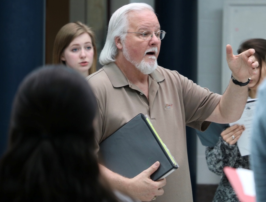 Dr. John Odom rehearses with his 7th period class in the rotunda. The band will perform its spring show on May 3, while various choral ensembles will perform on May 8. One aspect that makes the spring choral concert unique is that much of the show is student-created and student-conducted.