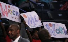 Three young girls display signs with one of the Atlanta Dream mottos. Several players own businesses or support causes outside of the WNBA, helping them serve as role models on and off the court.