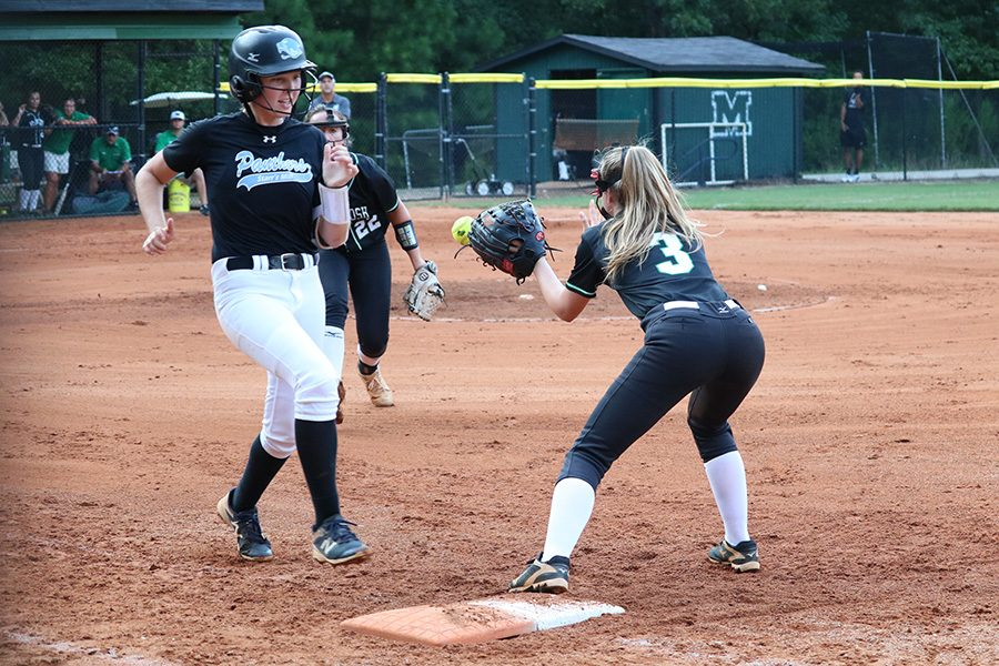 Junior Paige Andrews races to first base while Sophomore Chief Rebecca Muh attempts to throw her out. Muh and freshman Lady Panther Lilli Backes battled on the mound, but the Starr's Mill offense came through in the 3-0 win.
