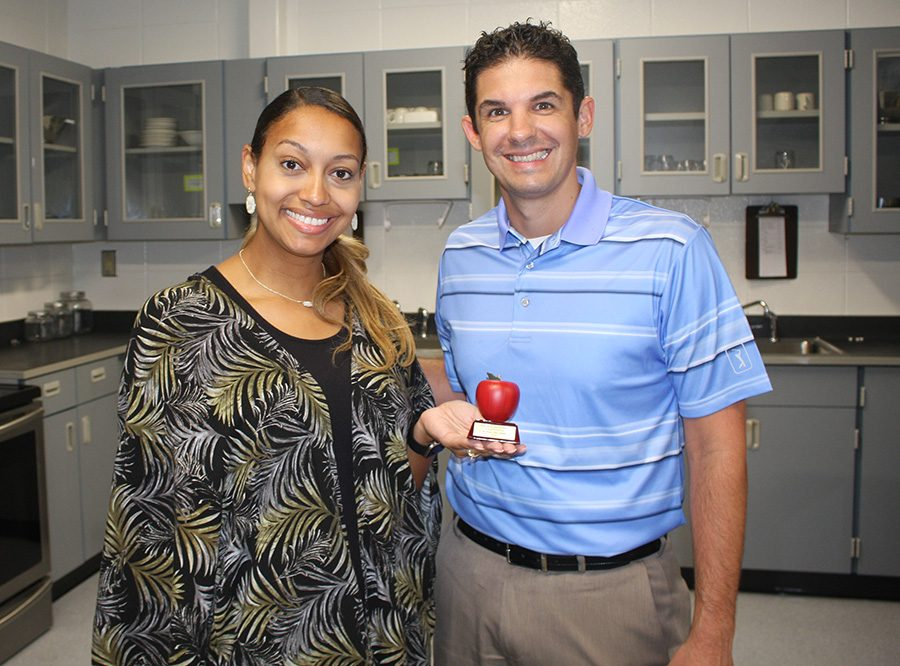 """Tim Monihan from Farmers Insurance in Peachtree City poses with this month's Golden Apple winner Adriah Williams. """"Students are people and teachers are people, and I think I'm drawn towards the teaching profession because I am a people person,"""" Williams said."""