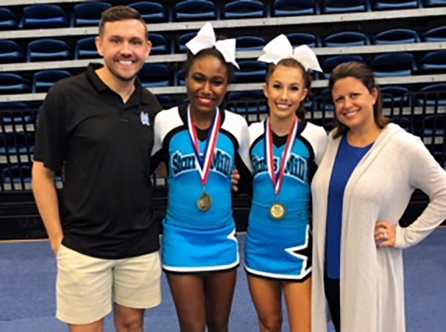 Coach Todd Saye (far left), varsity cheerleaders Tori Davis (middle left) and Hannah Defler (middle right), and head coach Heather McNally (far right) all gather together after the competition. Both girls advanced into the top 16. The winner of Cheerleader of the Year will be announced on Nov. 9.