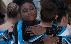 Senior cheerleader Tori Davis hugs a teammate before the team's routine. The varsity team placed first at the competition at Whitewater, while the JV team finished in third.