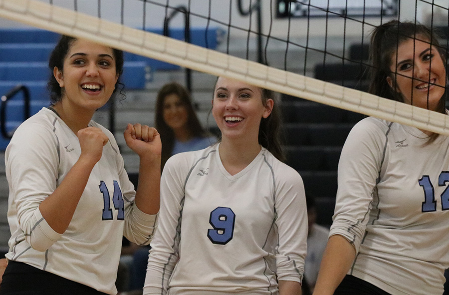 "Three members of the Mill smiling after a win in a best-of-five match against Westlake. They beat the Westlake Lions 25-7 in all three games. ""I love being with everyone and seeing everyone grow and develop as a team,"" senior Lauren Ratinaud said.  ""When we work together and when we talk, we're such a good team and everyone plays so well."""