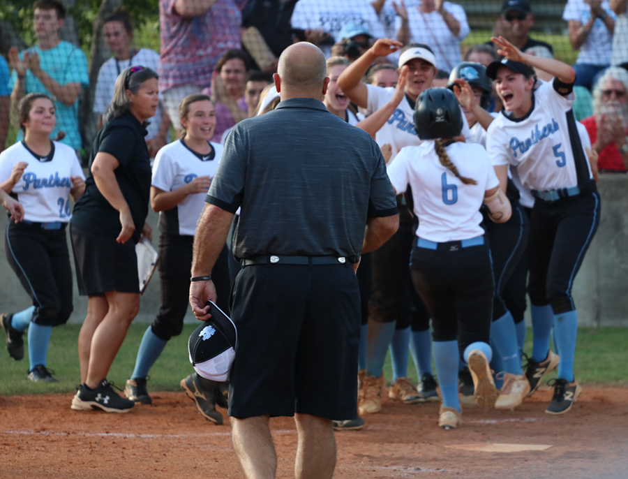 The Lady Panthers celebrate a home run from sophomore Jolie Lester. The home run was one of many runs scored in the Mill's 10-1 win over Wayne County.