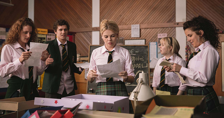 The Derry Girls in action. Erin (Saoirse-Monica Jackson), accompanied by friends Orla (Louisa Harland), James (Dylan Llewellyn), Clare (Nicola Coughlan), and Michelle (Jamie-Lee O'Donnell), address a dilemma facing the school newspaper.